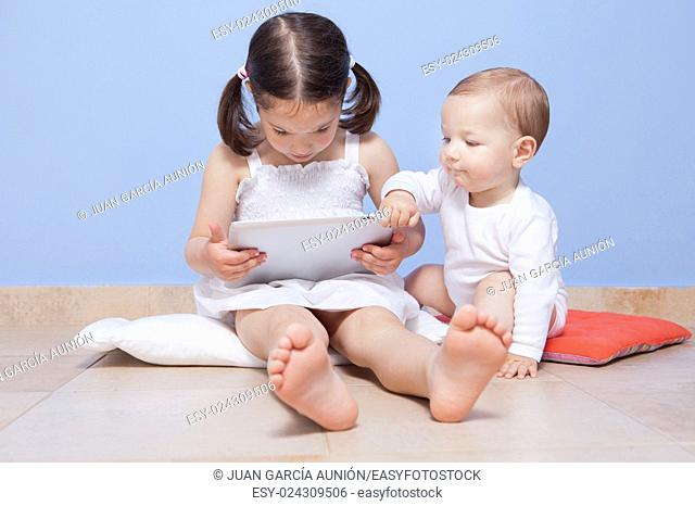 Baby boy discovering with her sister a tablet pc