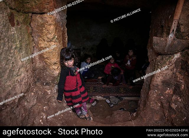 23 February 2020, Syria, Idlib: A Syrian child looks on as she stands inside a cave at Taltouna village. At least eight families live in an ancient deserted...
