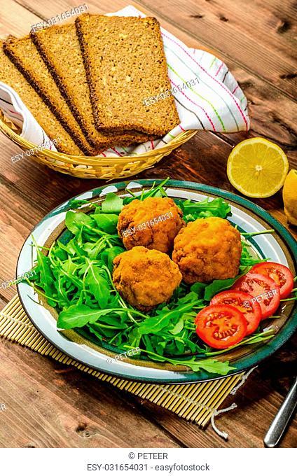 Macaroni and cheese balls, salad of arugula and healthy wholemeal bread