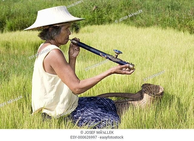 alte asiatische Frau mit Opiumpfeife