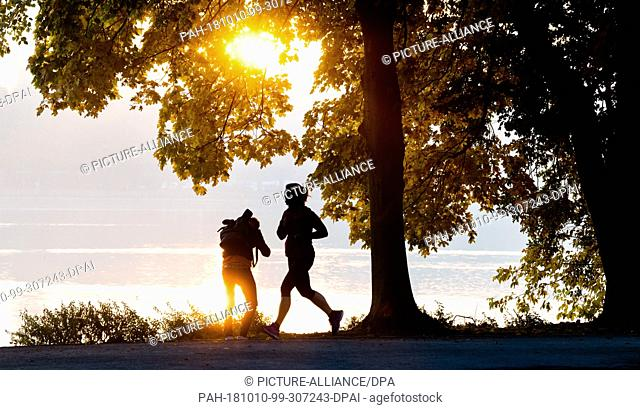 10 October 2018, Lower Saxony, Hanover: A jogger and a photographer enjoy a sunny autumn morning at the Maschsee. Photo: Julian Stratenschulte/dpa
