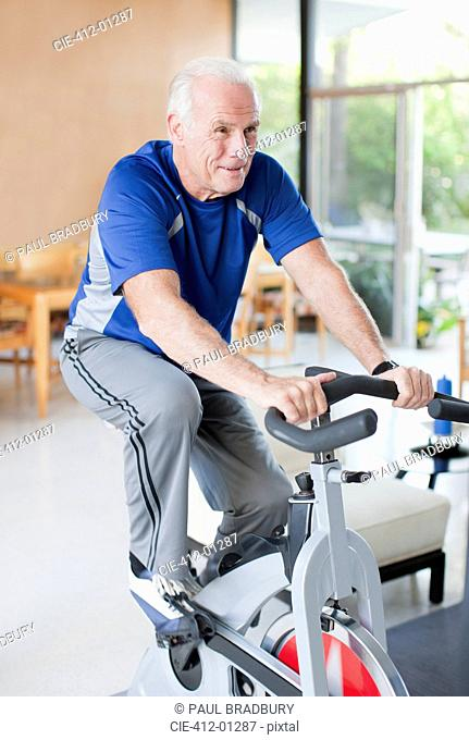 Older man riding exercise bike at home