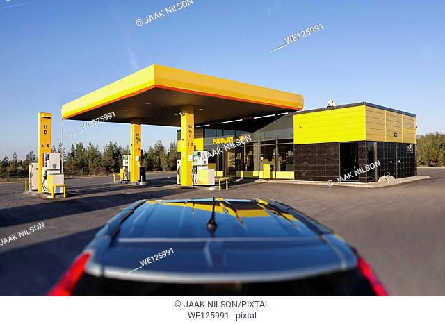 Car in gas station. Reflection on motor vehicle roof, tail-light. Convenience store in Estonia