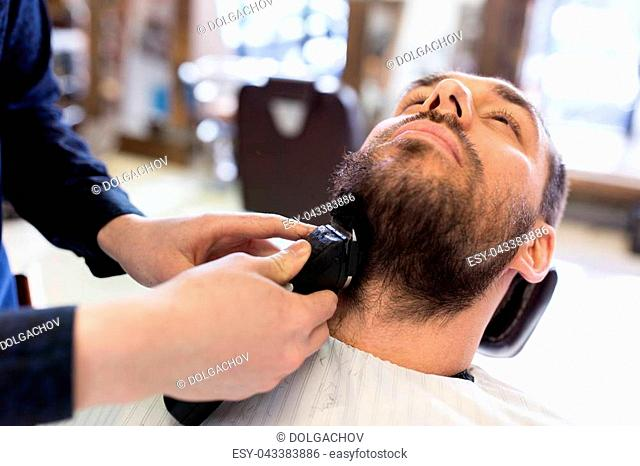 grooming and people concept - man and barber hands with trimmer or shaver cutting beard at barbershop