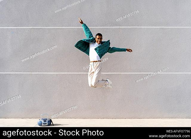 Carefree man jumping with arms outstretched against gray wall