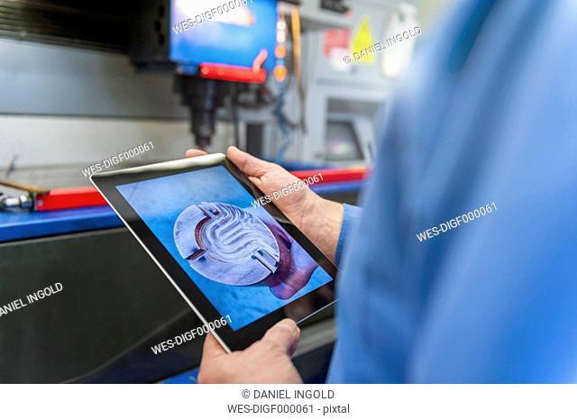 Man with digital tablet examining metal workpiece