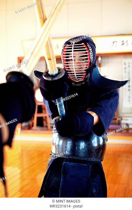 Two Japanese Kendo fighters wearing Kendo masks practicing with wood sword in gym