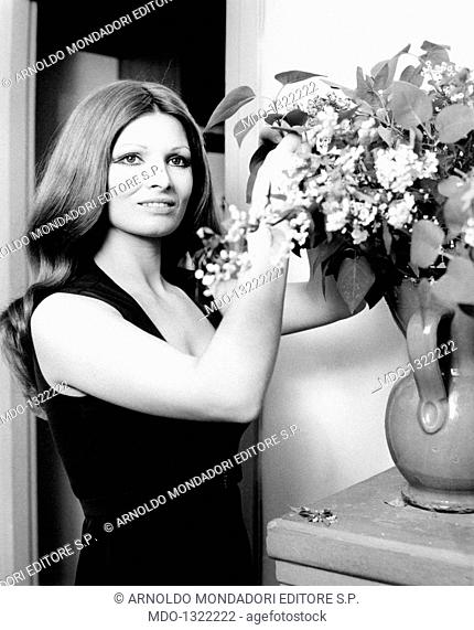 Portrait of Scilla Gabel smiling. Portrait of the Italian actress Scilla Gabel (Gianfranca Gabellini) smiling with a vase of flowers. Rome, May 1968