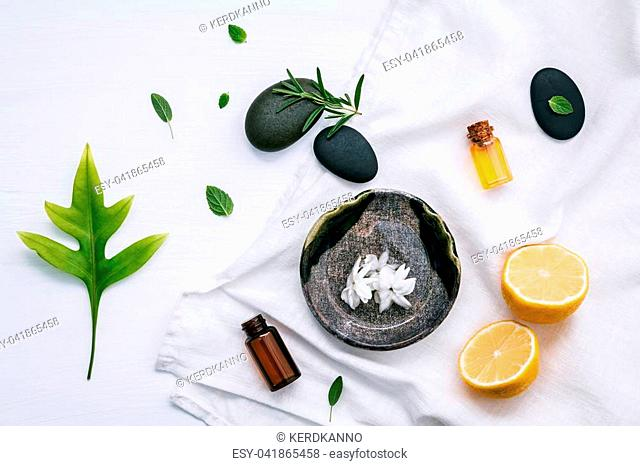 Alternative medicine and aromatherapy bottle of essential oil with fresh herbal rosemary, lemon and peppermint setup with flat lay on white wooden table
