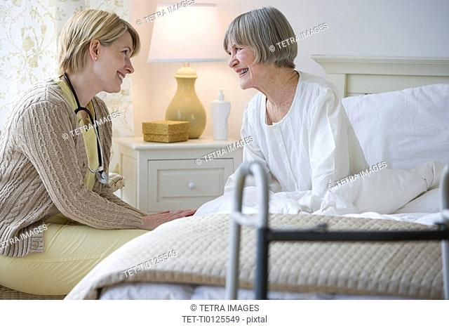 Nurse talking to senior woman in bed