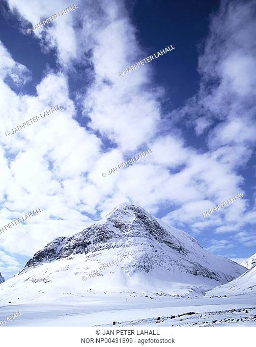Snow covered mountains and cloudy sky