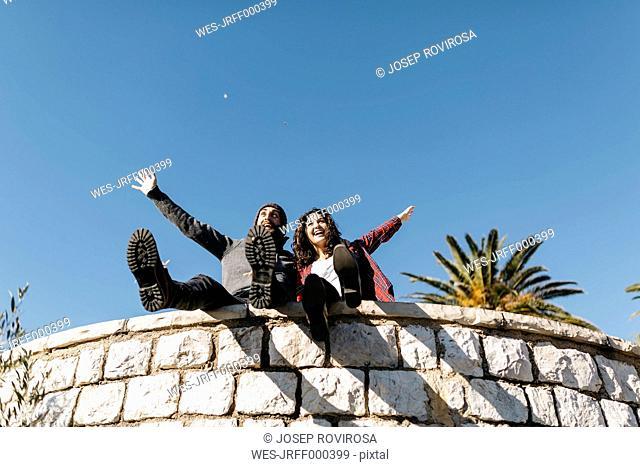 Spain, Tarragona, exuberant young couple sitting on stone wall