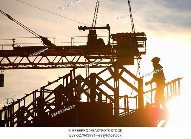 Construction worker, crane and building at sunset, France