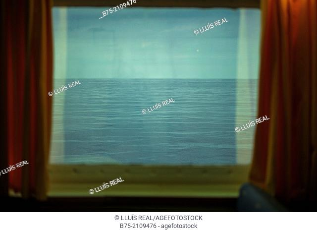 View of the sea and the sky through a window with red curtains, of a boat. Croosing the Mediterranean Sea from Ciutadella, Menorca to Alcudia, Mallorca