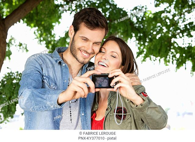 Couple taking a picture of themselves with a digital camera, Paris, Ile-de-France, France