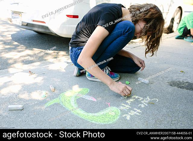 On Earth Day a teen girl draws on concrete with chalk