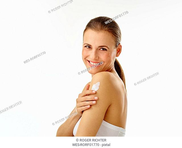 Young woman applying body creme on shoulder