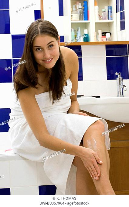 young woman in bathroom wrapped up in a towel, putting cream on her leg