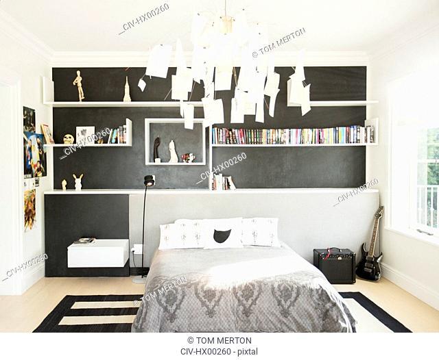 Modern paper chandelier hanging over bed in bedroom