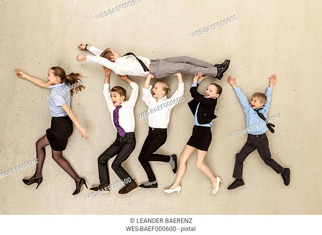 Business kids carrying boy in office