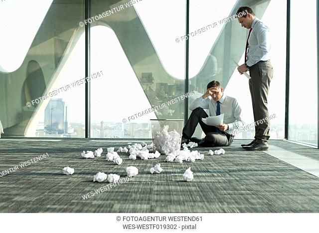 Two businessmen on office floor surrounded by crumpled paper