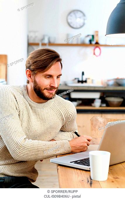 Mid adult man looking at laptop on table