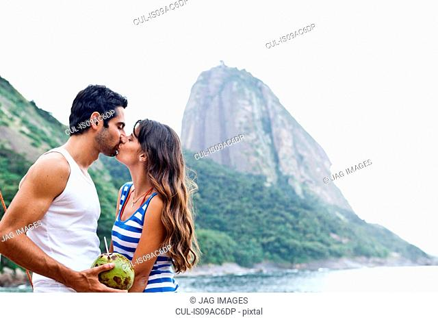 Couple kissing on beach with Sugarloaf Mountain, Rio de Janeiro, Brazil