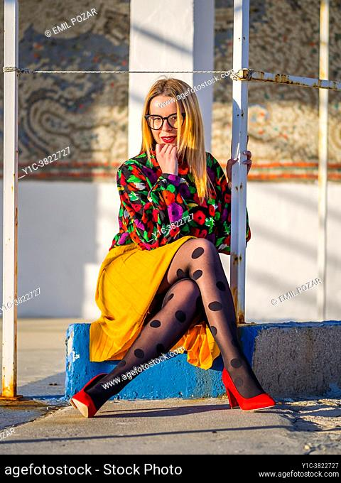 Young woman is sitting cross-legged looking at camera