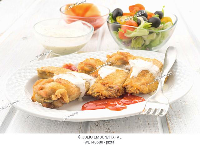 fried chicken wings with salad and sauces