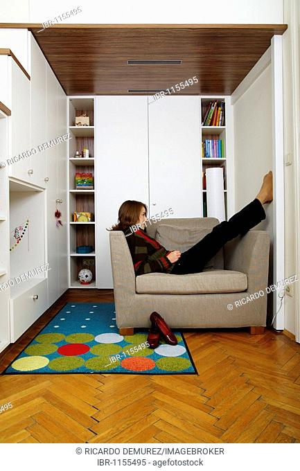 Young girl sitting on the armchair in her room