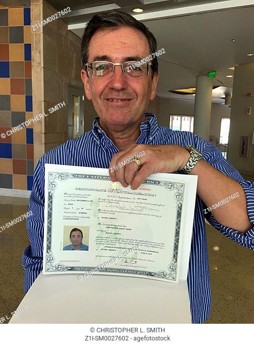 Adult man showing his U. S. Citizenship certificate after the Naturalization Cerimony in Tucson AZ