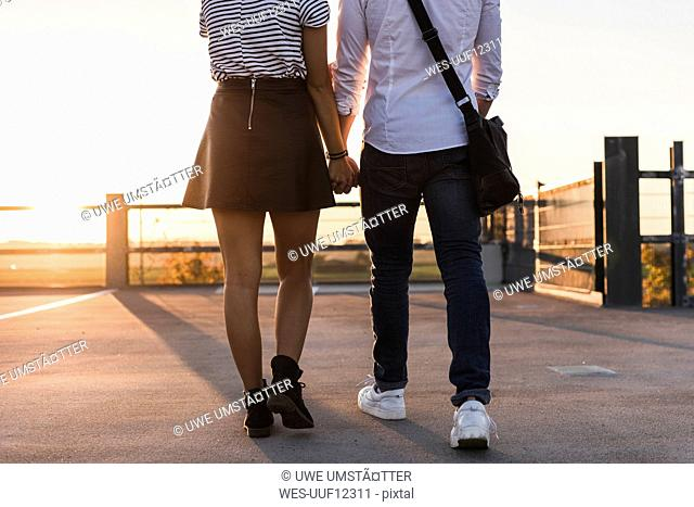 Young couple walking hand in hand on parking level at sunset