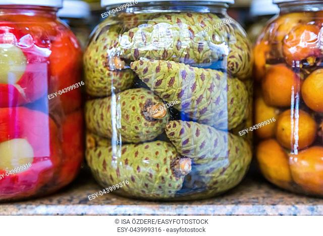 Green pine cones pickles are in glass jar display for sale