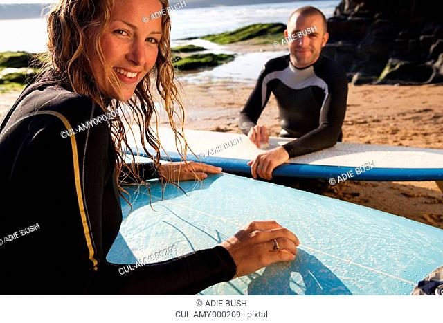 Couple waxing their surfboards smiling