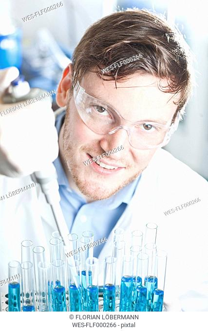 Germany, Young scientist pipetting blue liquid into test tubes, close up