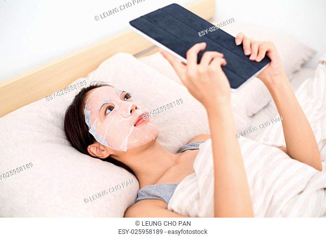 Woman using facial mask with tablet pc