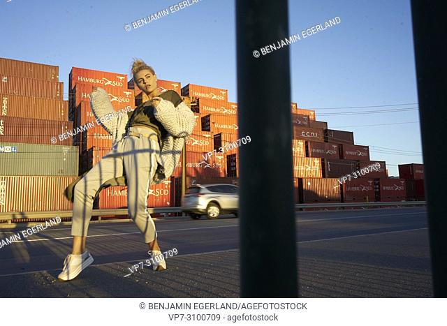 sensual woman dancing on street, in front of ship containers. Moving forward, travel, motion, car, feelings, sensitive. Blogger and actress Sarah Jeavons