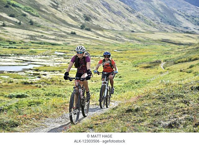 Women ride full suspension mountain bikes on the Resurrection Pass Trail in the Chugach National Forest, Kenai Peninsula, Southcentral Alaska