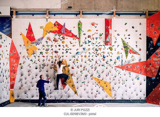 Climber guiding friend on climbing wall
