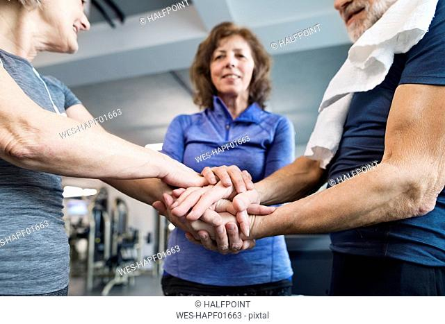 Group of fit seniors stacking hands in gym