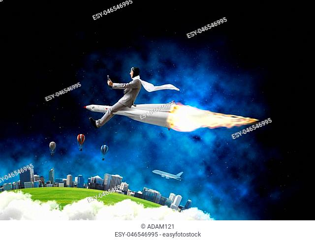 Conceptual image of young businessman in suit flying on rocket with planet Earth and open space on background