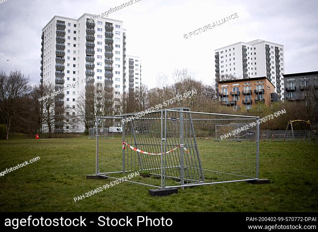 02 April 2020, Hamburg: With red and white barrier tape and surrounded by a mobile fence, the football goal is blocked on a meadow area in the Bahrenfeld...