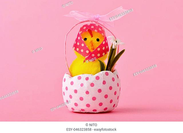 a funny lady teddy chick wearing a pink headscarf patterned with white dots emerging from a cracked white eggshell patterned with pink dots