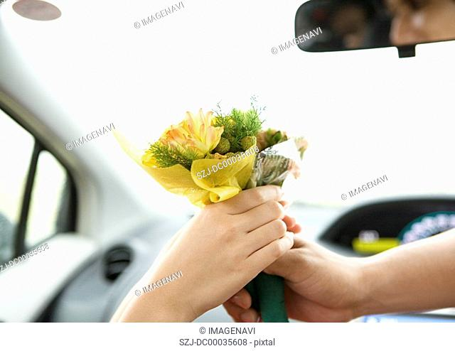 Close up of couple's hands giving a bouquet