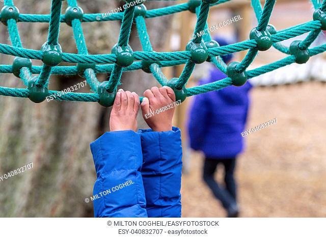 A young child hanging onto rope climbing equipment in Battersea Park, London