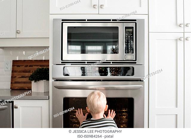 Young boy in kitchen looking through oven door