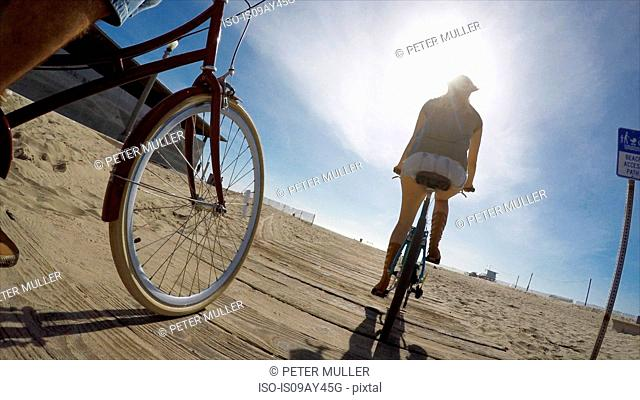 Low angle view of couple cycling on boardwalk at Venice Beach, California, USA