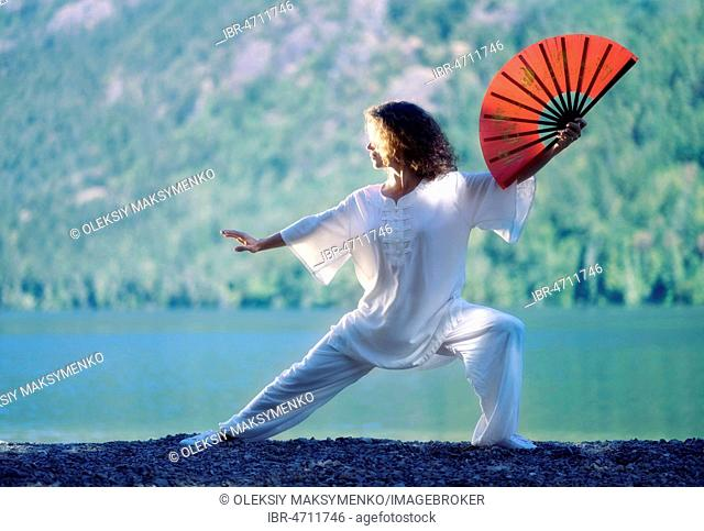 Young woman practicing Tai Chi Chuan with a red fan at mountain lake shore in the nature