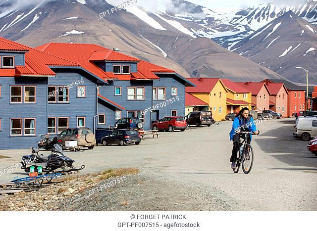 WOMAN ON A BIKE AND COLORFUL WOODEN HOUSES, CITY OF LONGYEARBYEN, THE NORTHERNMOST CITY ON EARTH, SPITZBERG, SVALBARD, ARCTIC OCEAN, NORWAY