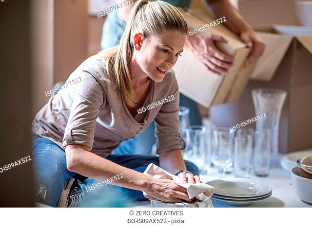 Moving house: woman wrapping glassware in paper before packing